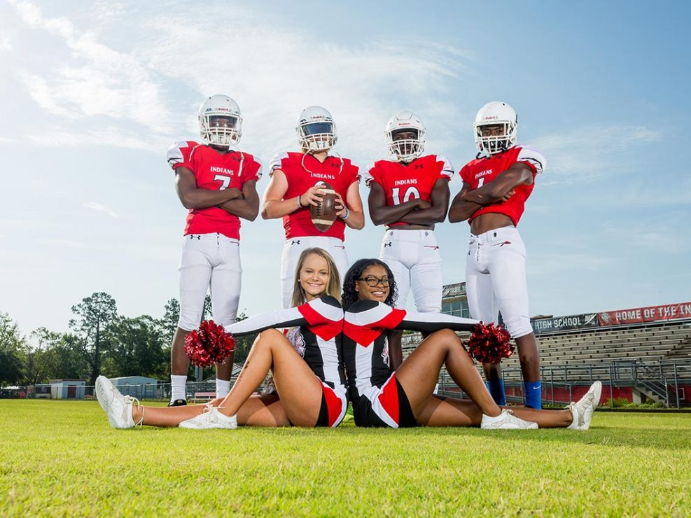 Athletic Gallery - Four football players and two cheerleaders on field