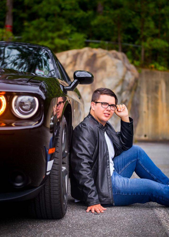Isaac Salomon - Man in black leather jacket sitting beside black car