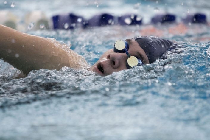 Avery Lee Photography - swimmer wearing head cap and goggle paddling at pool
