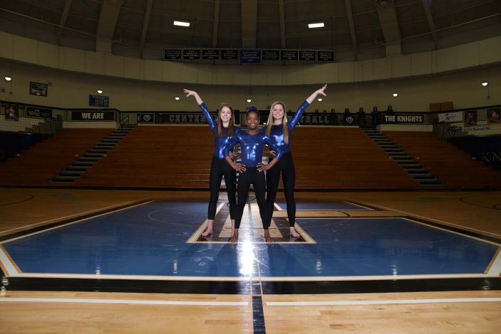 Isaac Salomon - Three people in cheerleading outfit posing in basketball court